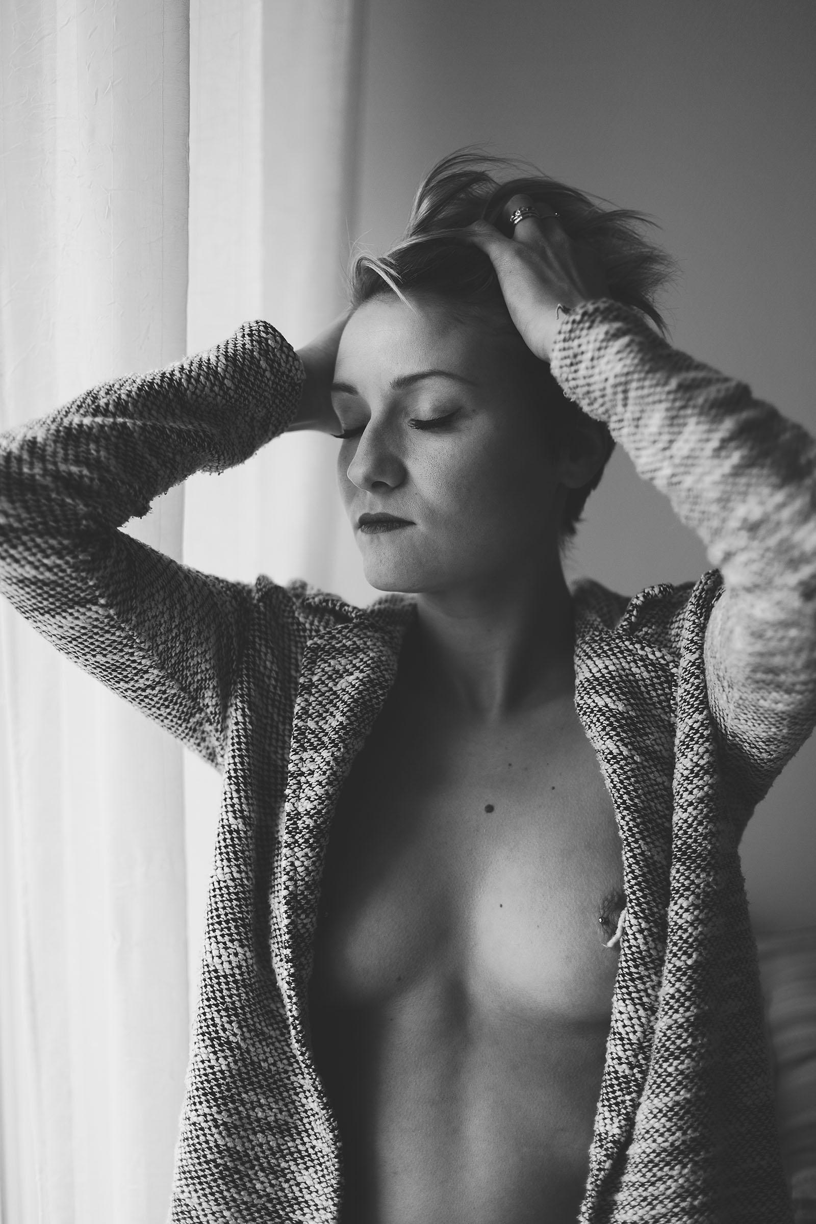 Une idée cadeau originale à Lyon Justine beau portrait noir et blanc femme seins nus qui passe la main dans ses cheveux. Blueberry corner photographe professionnel à Lyon et Clermont ferrand spécialisé dans la photo de charme, photo glamour et boudoir