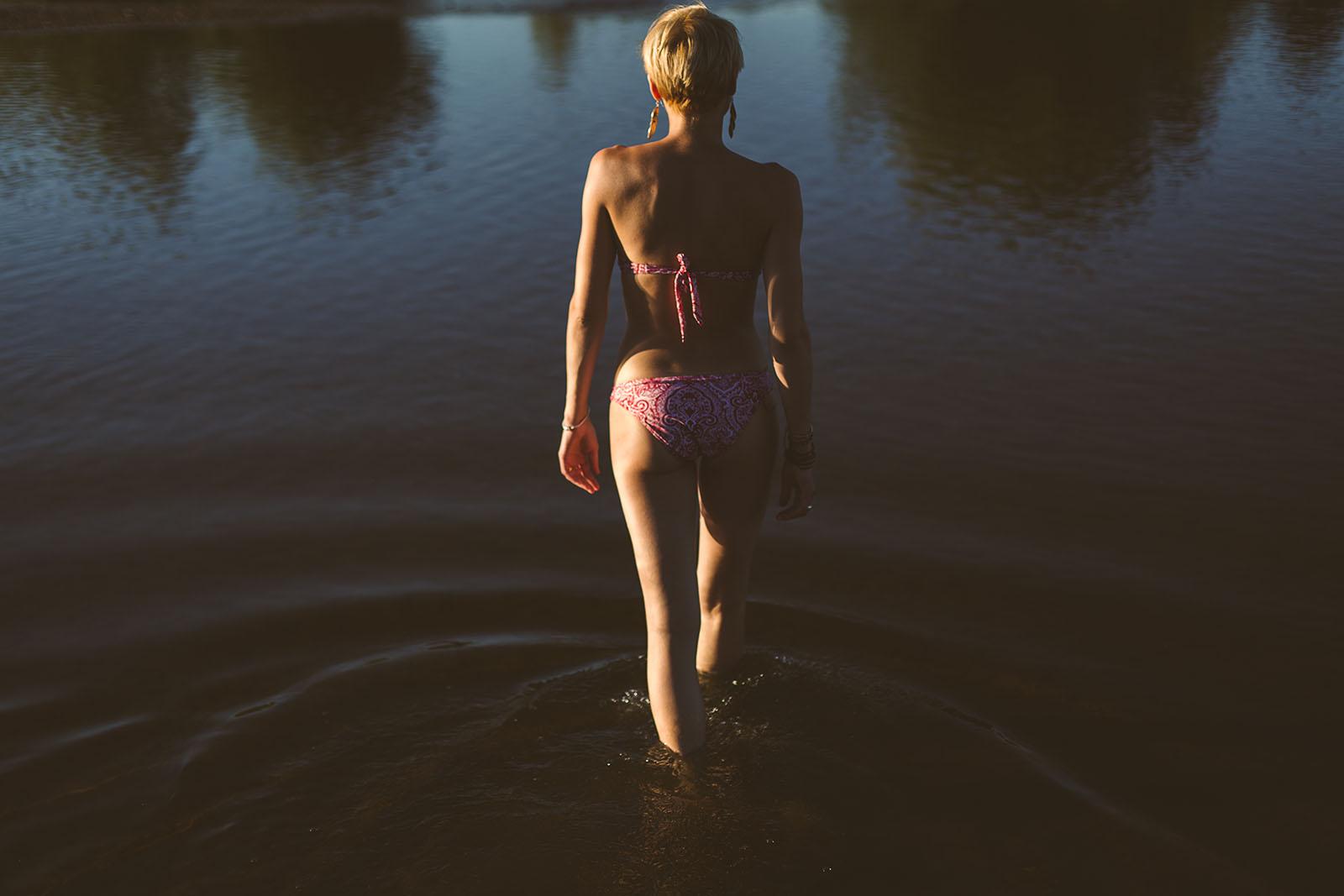Séance photo intime en extérieur portrait femme marchant dans l'eau en maillot de bain