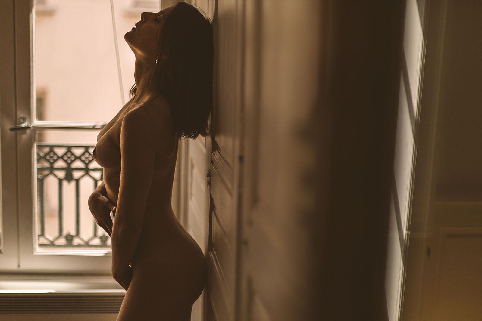 Du glamour, des courbes et une belle lumière Séance photo glamour à Lyon femme nue devant une fenêtre se donnant du plaisir et caressant son corps