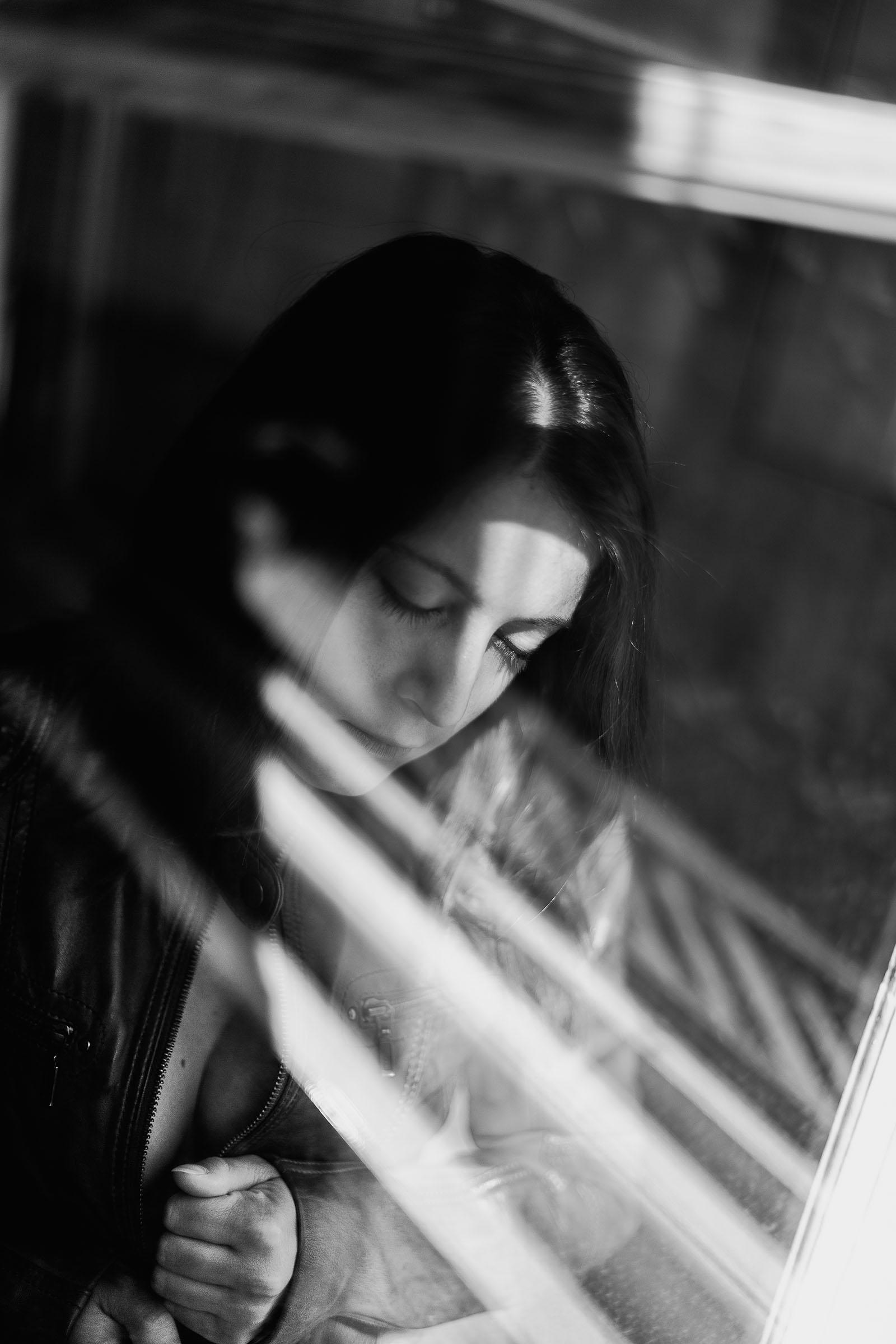 Du glamour, des courbes et une belle lumière séance photo glamour à Lyon, femme sensuelle avec le reflet d'une fenêtre une veste en cuir cachant ses seins