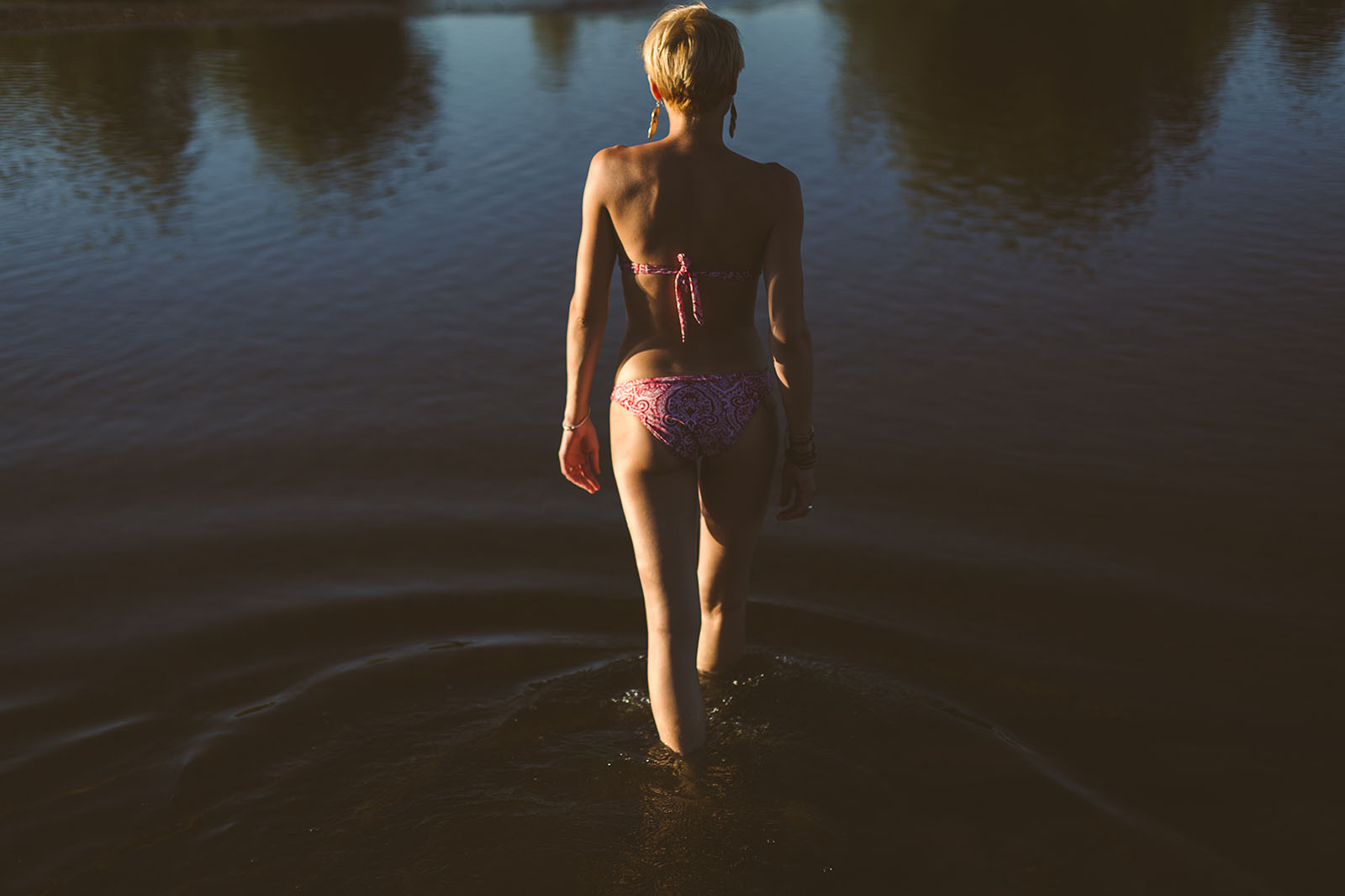 Glamorous photoshoot in outdoor photo shoot intimate outdoor portrait woman walking in water in a swimsuit