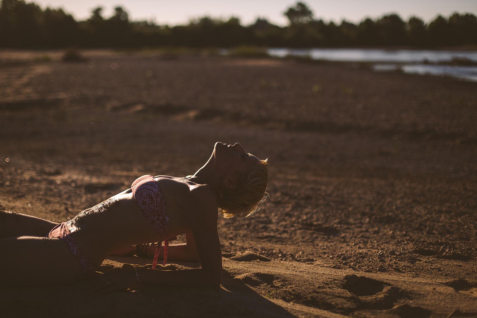 Séance photo intime en extérieur femme en lingerie allongée sur le sable