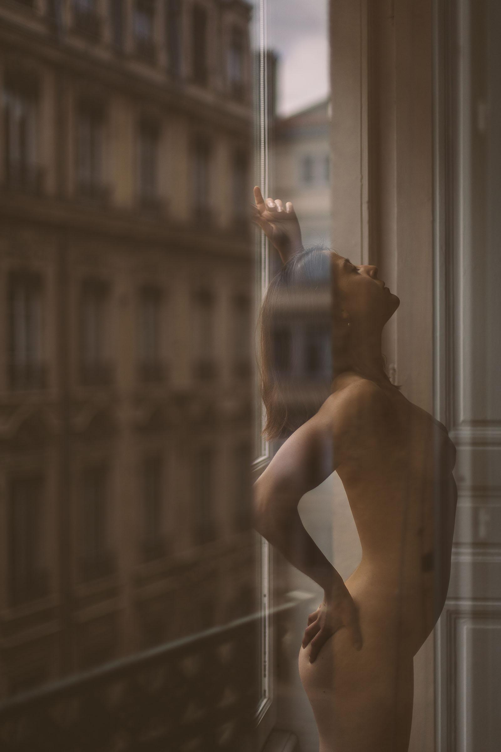 Du glamour, des courbes et une belle lumière séance photo sensuel à Lyon femme nue devant une fenêtre avec les reflets de la ville